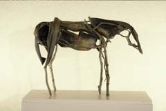 Deborah Butterfield (b. 1949). Untitled (1992). Bronze, 15 1/4 x 24 x 36 inches. Purchased with funds donated by the Kemper Foundations. This sculpture is an example of Deborah Butterfield's interest in using abstracted animal forms to engage the viewer. A lifelong interest with horses influences her choice of subject. Using a variety of materials, Butterfield has created pieces that retain the original forms of the materials while depicting both the exterior and interior lines of the animal. This work in Albrecht-Kemper collection is cast in bronze, a durable medium for a work that appears instead to be a fragile mixture of natural materials like leaves and branches that also suggest the muscles, bones, and skin of the horse itself.